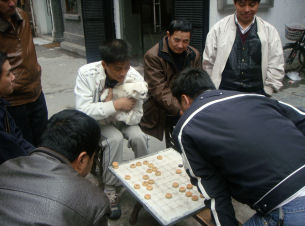 Chess players in a small street. One is holding his dog